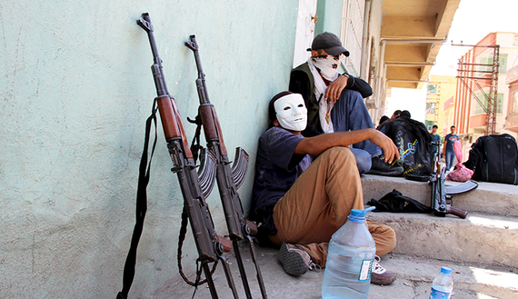 Masked members of YDG-H, youth wing of the outlawed Kurdistan Workers Party (PKK), sit next to their weapons in Silvan, near the southeastern city of Diyarbakir, Turkey, August 17, 2015. The PKK has attacked military targets on a near-daily basis since the Turkish government launched air strikes on rebel camps in northern Iraq on July 25, wrecking a two-year-old ceasefire. REUTERS/Sertac Kayar TPX IMAGES OF THE DAY - RTX1OICG